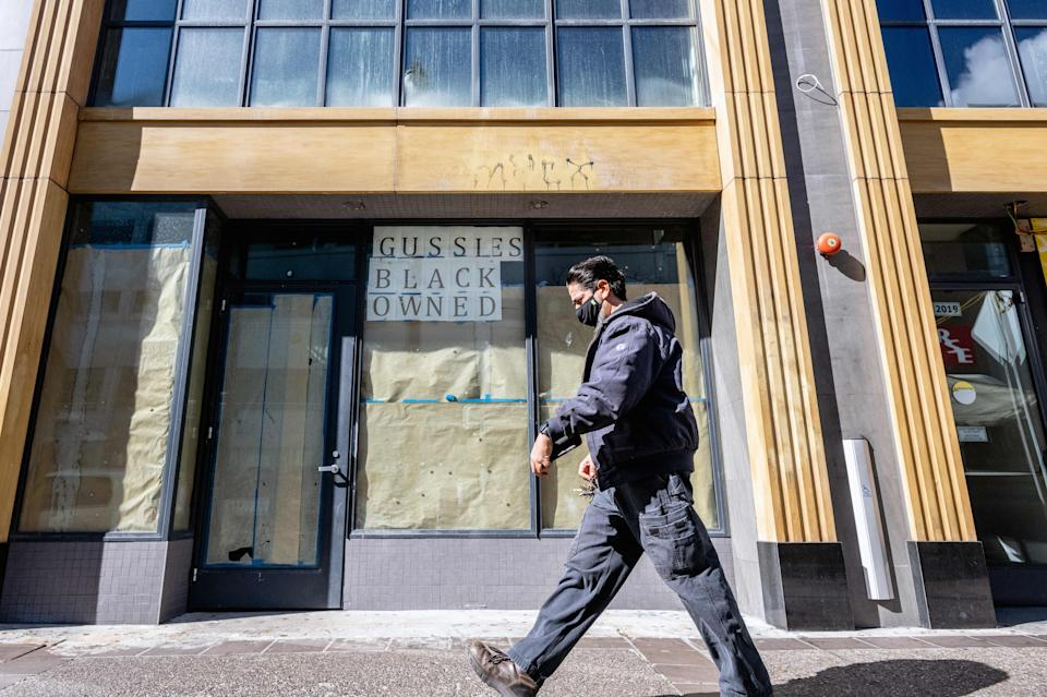 A person walks by a boarded-up shop with a