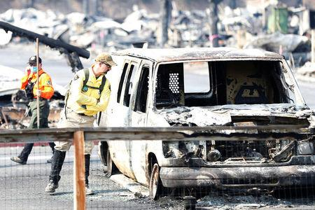 An urban search and rescue team member of the Monterey County Sheriff's Office peeks into a burned out vehicle during a search for two missing people at the Journey's End Mobile Home Park destroyed by the Tubbs Fire in Santa Rosa, California, U.S. October 13, 2017. REUTERS/Stephen Lam