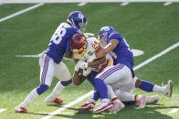 Washington Football Team running back Antonio Gibson (24) is tackled by New York Giants' Blake Martinez (54) and Montre Hartage (18) during the second half of an NFL football game Sunday, Oct. 18, 2020, in East Rutherford, N.J. (AP Photo/John Minchillo)