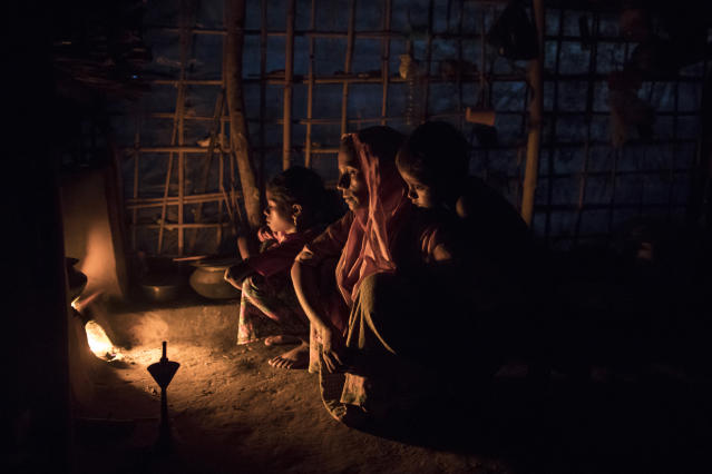 <p>Rohingya Muslim refugees who have been living in Bangladesh for over a year sit by a fire in a more established shelter in a refugee camp on Sept. 8, 2017 in Gundum, Bangladesh. (Photo: Dan Kitwood/Getty Images) </p>