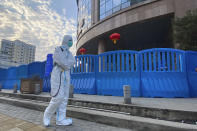 "A worker in protectively overalls and disinfecting equipment walks outside the Wuhan Central Hospital where Li Wenliang, the whistleblower doctor who sounded the alarm and was reprimanded by local police for it in the early days of Wuhan's pandemic, worked in Wuhan in central China's Hubei province on Saturday, Feb. 6, 2021. Dr. Li Wenliang died in the early hours of Feb. 7 from the virus first detected in this Chinese city. A small stream of people marked the anniversary at the hospital. The 34-year-old became a beloved figure and a potent symbol in China after it was revealed that he was one the whistleblowers who authorities had punished early for ""spreading rumors"" about a SARS-like virus. (AP Photo/Ng Han Guan)"