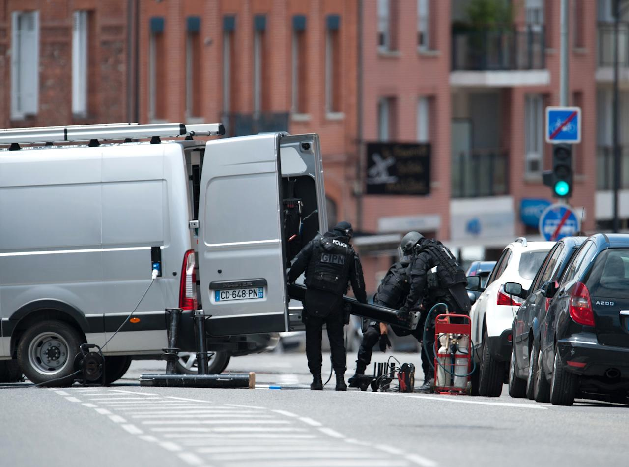 Elite police officers unload items next to a bank where a man took hostages in the southern French city of Toulouse, Wednesday, June 20, 2012. A gunman who authorities say had past psychiatric problems took four people hostage Wednesday in a bank in the southern French city of Toulouse, claiming he was acting for religious reasons. (AP Photo/Bruno Martin)