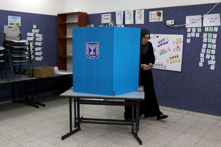 An Israeli-Arab woman walks out from behind a voting booth as Israelis vote in a parliamentary election, at a polling station in Umm al-Fahm, Israel April 9, 2019. REUTERS/Ammar Awad