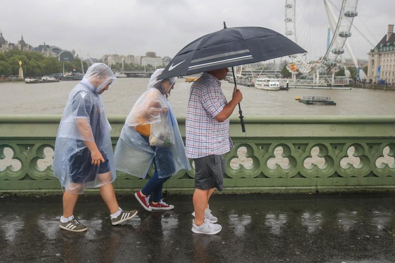 Pedestrians on Westminster Bridge with rain ponchos and an umbrella during rain showers as a month's rainfall was expected in three hours with the risk of flooding in some areas of the United Kingdom. (Photo by Amer Ghazzal / SOPA Images/Sipa USA)