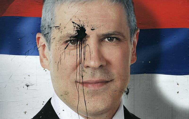 FILE - Jan. 27, 2008 file photo of a pre-election poster of Serbia's President Boris Tadic splattered with paint, in Belgrade, Serbia. Tadic said Wednesday April 4 2011 that he is resigning, paving the way for an early presidential election where he will face a strong challenge from a nationalist candidate. In the presidential vote, Tadic will be challenged by nationalist candidate Tomislav Nikolic who has received tacit support from Russia. (AP Photo/Darko Vojinovic, file)