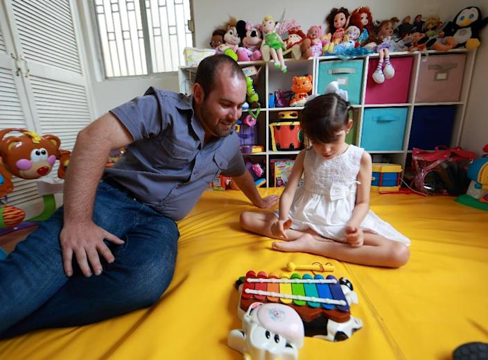 Graciela, who suffers from a severe form of epilepsy, plays with her father Raul Elizalde at their house in the Guadalupe municipality near Monterrey (AFP Photo/Carlos Ramirez)