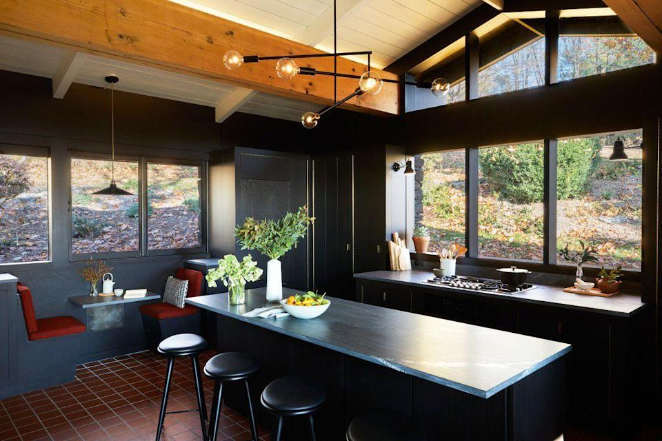 """<p>These single-seat banquettes and built-in metal table in a kitchen by <a href=""""https://www.grtarchitects.com/"""" rel=""""nofollow noopener"""" target=""""_blank"""" data-ylk=""""slk:GRT Architects"""" class=""""link rapid-noclick-resp"""">GRT Architects</a> are reminiscent of a classic midcentury diner right off the highway—perfect for this inky and sophisticated kitchen in a midcentury modern home New York's Hudson Valley. </p>"""