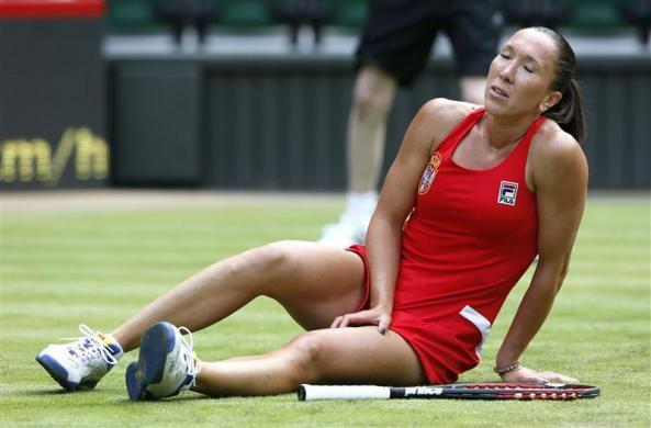 Jelena Jankovic of Serbia slips and falls in her women's singles tennis match against Serena Williams of the United States at the All England Lawn Tennis Club during the London 2012 Olympics Games July 28, 2012.