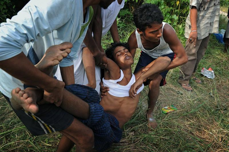 A rescued migrant is carried to a waiting ambulance upon his arrival on May 15, 2015 at a confinement area in Indonesia's Kuala Langsa, where hundreds of migrants from Myanmar and Bangladesh are taking shelter (AFP Photo/Chaideer Mahyuddin)