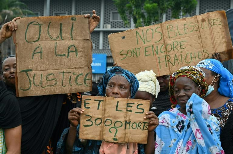 Demonstrators at a small anti-Gbagbo protest in Abidjan last month. The placards read: 'Yes to justice,' 'Our wounds are still open' and 'What about the 3,000 dead?'