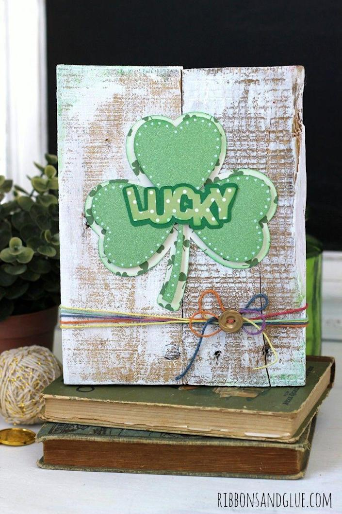 """<p>This project can be made in just a few steps with a silhouette, using hot glue to adhere the lucky sign to the pallet. And don't forget the cute rainbow twine and gold button at the bottom!</p><p><strong>Get the tutorial at <a href=""""https://www.ribbonsandglue.com/shamrock-pallet-art.html"""" rel=""""nofollow noopener"""" target=""""_blank"""" data-ylk=""""slk:Ribbons & Glue"""" class=""""link rapid-noclick-resp"""">Ribbons & Glue</a>.</strong></p><p><strong><a class=""""link rapid-noclick-resp"""" href=""""https://www.amazon.com/gp/product/B00HFFAKSA/?tag=syn-yahoo-20&ascsubtag=%5Bartid%7C2164.g.35012898%5Bsrc%7Cyahoo-us"""" rel=""""nofollow noopener"""" target=""""_blank"""" data-ylk=""""slk:SHOP RAINBOW TWINE"""">SHOP RAINBOW TWINE</a><br></strong></p>"""