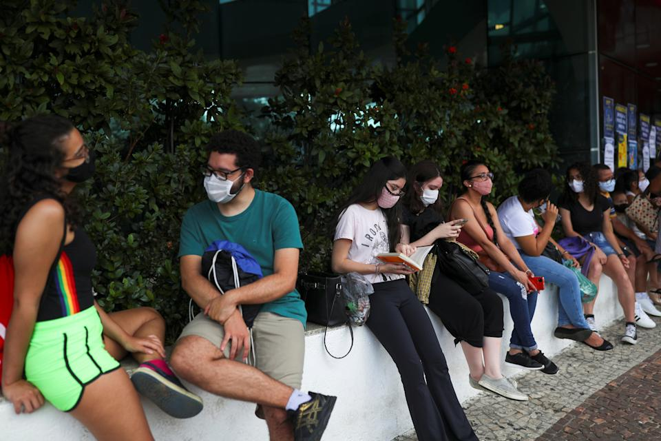 A student reads a book as people gather before the beginning of the ENEM, Exame Nacional do Ensino Medio (National High School Exam), during the outbreak of the coronavirus disease (COVID-19), at UNIP Vergueiro test site in Sao Paulo, Brazil January 17, 2021. REUTERS/Amanda Perobelli