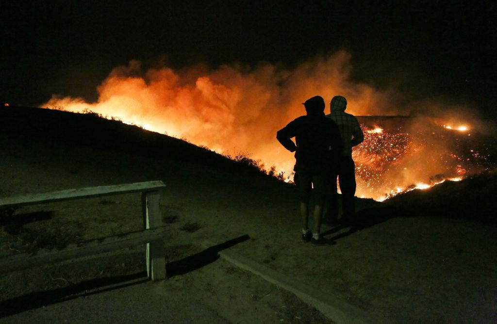 <p>People view the Creek Fire burn on a hillside in the Shadow Hills neighborhood in Los Angeles, California. Strong Santa Ana winds are rapidly pushing multiple wildfires across the region, expanding across tens of thousands of acres and destroying hundreds of homes and structures. (Mario Tama/Getty Images) </p>