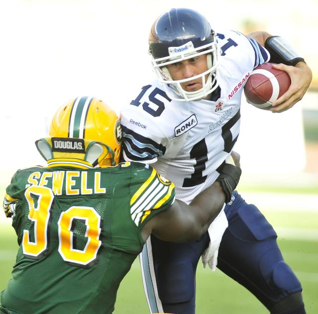left to right - Edmonton Eskimos player # 90 ( DL) Almondo Sewell goes for the sack on Toronto Argonauts player # 15 (QB ) Ricky Ray during the 4th quarter of CFL game action between the Edmonton Eskimo's and the Toronto Argonauts at Commonwealth stadium in Edmonton June 30/2012 (CFL PHOTO / Walter Tychnowicz)