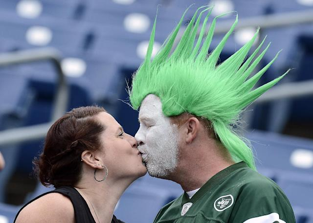 New York Jets fans Ana Hall and Rick Martin kiss as they watch players warm up before an NFL football game between the Jets and the Tennessee Titans on Sunday, Sept. 29, 2013, in Nashville, Tenn. (AP Photo/Mark Zaleski)