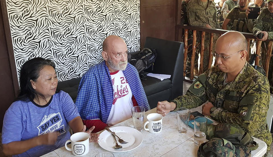In this photo provided by Armed Forces of the Philippines, Task Force Sulu, Philippine Maj. Gen. Corleto Vinluan, right, talks to rescued British national Allan Hyrons, center, and his Filipino wife Wilma inside a military camp at Jolo, Sulu province, southern Philippines on Monday Nov. 25, 2019. A Philippine general says troops have rescued the British man and his Filipino wife who were abducted by gunmen in their beach resort in the south last month and taken to the jungle hideouts of local militants allied with the Islamic State group. (Armed Forces of the Philippines, Joint Task Force Sulu via AP)