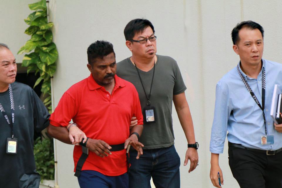 Murder suspect Krishnan Raju (in red) being escorted by police to the Loyang Gardens condominium where he allegedly killed a 44-year-old woman believed to be his wife. (PHOTO: Hannah Teoh / Yahoo News Singapore)