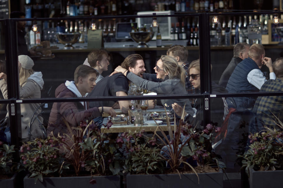 FILE - In this Saturday, April 4, 2020 file photo a couple hug and laugh as they have lunch in a restaurant in Stockholm, Sweden. Sweden's relatively low-key approach to coronavirus lockdowns captured the world's attention when the pandemic first hit Europe. But it also had a per capita death rate much higher than other Nordic countries. Now, as infection numbers surge in much of Europe, Sweden has some of the lowest numbers of new cases and there are only 14 people being treated for the virus in intensive care in the country of 10 million.(AP Photo/Andres Kudacki, File)