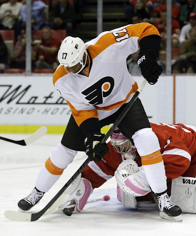 Detroit Red Wings goalie Jimmy Howard, bottom, stops a shot by Philadelphia Flyers right wing Wayne Simmonds (17) during the first period of an NHL hockey game in Detroit, Saturday, Oct. 12, 2013. (AP Photo/Carlos Osorio)