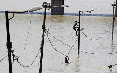 A boy climbs a partially submerged electric pole as he plays with others on the flooded banks of Ganga river, in Allahabad, India, August 21, 2016. REUTERS/Jitendra Prakash