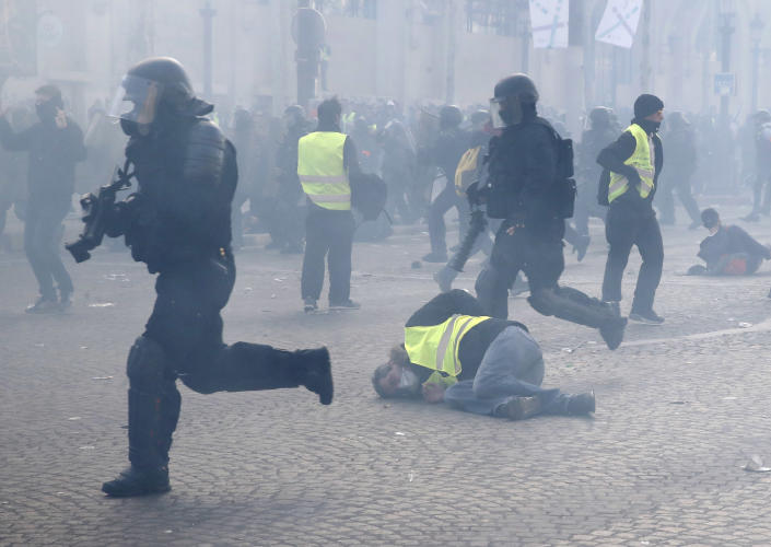 FILE - In this March 16, 2019 file photo, riot police officers charge as a yellow vests demonstrator falls in Paris. Paris police say more than 100 people have been arrested amid rioting in the French capital by yellow vest protesters and clashes with police. As videos helped reveal many cases of police brutality, French civil rights activists voiced fears that a new security law would threaten efforts by people from minorities and poor neighborhoods to document incidents involving law enforcement officers. French President Emmanuel Macron's government is pushing a new security bill that would notably make it illegal to publish images of officers with intent to cause them harm. (AP Photo/Christophe Ena, File)