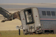 A piece of heavy equipment props up a leaning train car, Sunday, Sept. 26, 2021, that was part of an Amtrak train that derailed Saturday, near Joplin, Mont. The westbound Empire Builder was en route to Seattle from Chicago with two locomotives and 10 cars. (AP Photo/Ted S. Warren)
