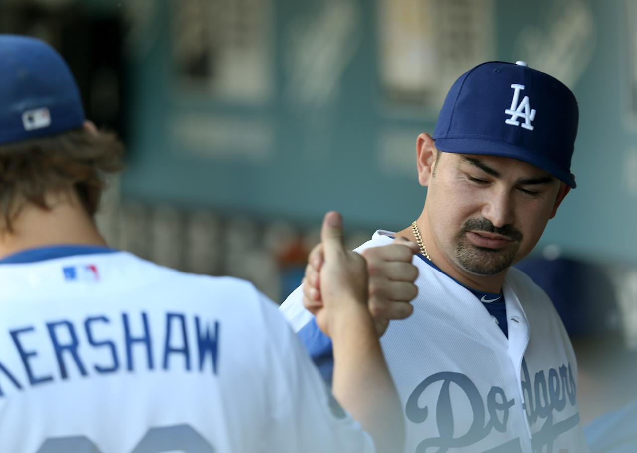 LOS ANGELES, CA - AUGUST 25:  First baseman Adrian Gonzalez #23 of the Los Angeles Dodgers bumps fists with starting pitcher Clayton Kershaw #22in the dugout before the game with the Miami Marlins on August 25, 2012 at Dodger Stadium in Los Angeles, California.  (Photo by Stephen Dunn/Getty Images)