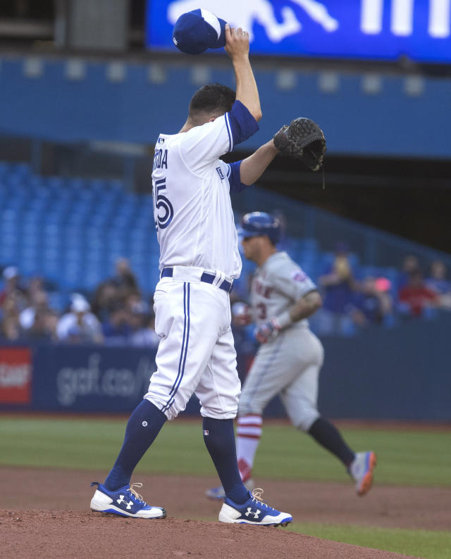 Toronto Blue Jays starting pitcher Marco Estrada walks off the mound after giving up a two-run home run to New York Mets' Asdrubal Cabrera, rear, during the first inning of a baseball game Tuesday, July 3, 2018, in Toronto. (Fred Thornhill/The Canadian Press via AP)