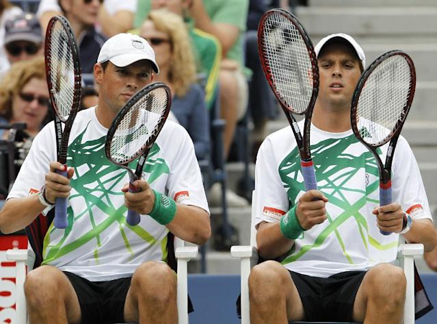FILE - In this Sept. 10, 2010 file photo, Bob Bryan, left, and his brother Mike Bryan look at their rackets before their men's doubles finals match at the U.S. Open tennis tournament in New York. Top-seeded Bob and Mike Bryan made their earliest exit from the Australian Open in 11 years, losing to American Eric Butorac and South African Raven Klaasen in the third round of the men's doubles 7-6 (9), 6-4 on Monday, Jan. 20, 2014. (AP Photo/Mark Humphrey, File)