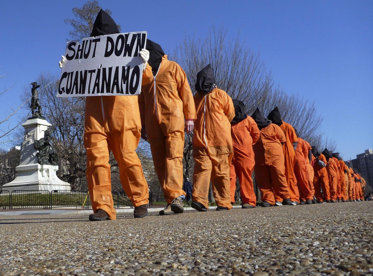 "Members of the group ""Witness Against Torture"" dressed in orange prison jump suits protest against the detention camp at Guantanamo Bay, along Pennsylvania Avenue in Washington D.C. January 10, 2012.  REUTERS/Larry Downing"