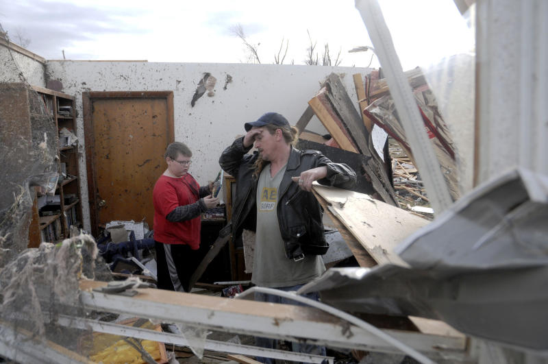 Gene Byrd pauses for a moment while he and his son Devyn Byrd, 14, look over some of the damage sustained to a friends house after a severe storm hit in the early morning hours on Wednesday, Feb. 29, 2012, in Harrisrbug, Ill. A severe pre-dawn storm pounded portions of southern Illinois on Wednesday. Several deaths have been reported in Harrisburg and left the city's medical center scrambling to treat an influx of injured, the hospital's top administrator said. (AP Photo/The Southern Illinoisan,Paul Newton )