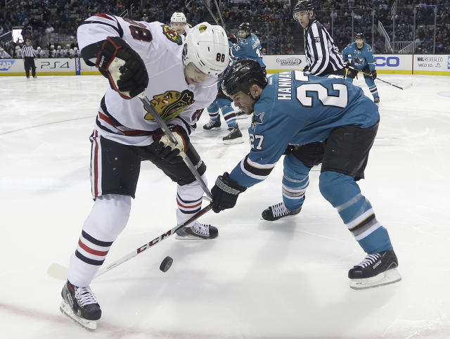 Chicago Blackhawks right wing Patrick Kane (88) tangle up for the puck against San Jose Sharks defenseman Scott Hannan (27) during the second period of an NHL hockey game in San Jose, Calif., Saturday, Feb. 1, 2014. (AP Photo/Tony Avelar)