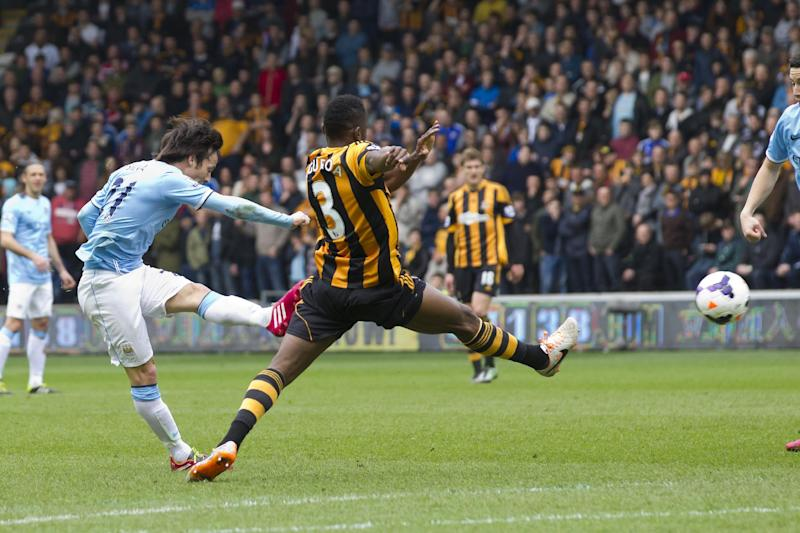Manchester City's David Silva, left, scores against Hull City during their English Premier League soccer match at the KC Stadium, Hull, England, Saturday March 15, 2014. (AP Photo/Jon Super)