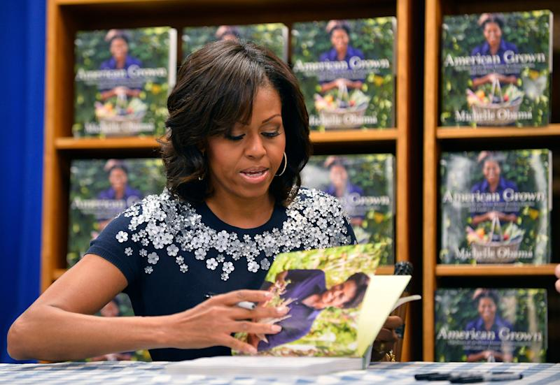 US First Lady Michelle Obama signs a copy of her book 'American Grown: The Story of the White House Kitchen Garden and Gardens Across America,' during a book signing event at Politics & Prose in Washington, DC, on May 7, 2013. Photo credit: JEWEL SAMAD/AFP/Getty Images