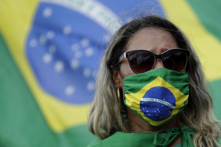A supporter of Brazilian President Jair Bolsonaro takes part in a gathering to commemorate the 1964 military coup that established a decades-long dictatorship, in the Ministries Esplanade in Brasilia, Brazil, Wednesday, March 31, 2021. The leaders of all three branches of Brazil's armed forces jointly resigned on Tuesday following Bolsonaro's replacement of the defense minister, causing widespread apprehension of a military shakeup to serve the president's political interests. (AP Photo/Eraldo Peres)