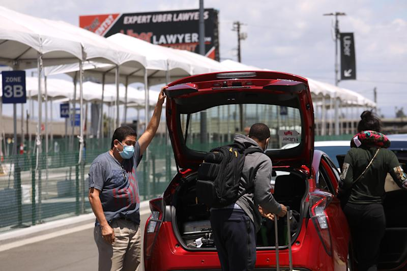 LOS ANGELES, CA - MAY 19, 2020 - - An Uber driver picks up passengers a day after Uber Technologies, Inc. cut 3,000 jobs as their business has been gutted by the coronavirus at Los Angeles International Airport on May 19, 2020. (Genaro Molina / Los Angeles Times via Getty Images)