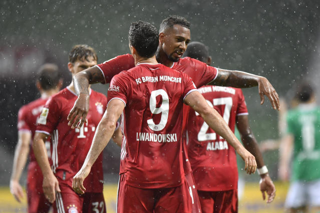 Bayern's Robert Lewandowski, foreground, celebrates with his teammate Bayern's Jerome Boateng after scoring his side's opening goal during the German Bundesliga soccer match between Werder Bremen and Bayern Munich in Bremen, Germany, Tuesday, June 16, 2020. Because of the coronavirus outbreak all soccer matches of the German Bundesliga take place without spectators. (AP Photo/Martin Meissner, Pool)