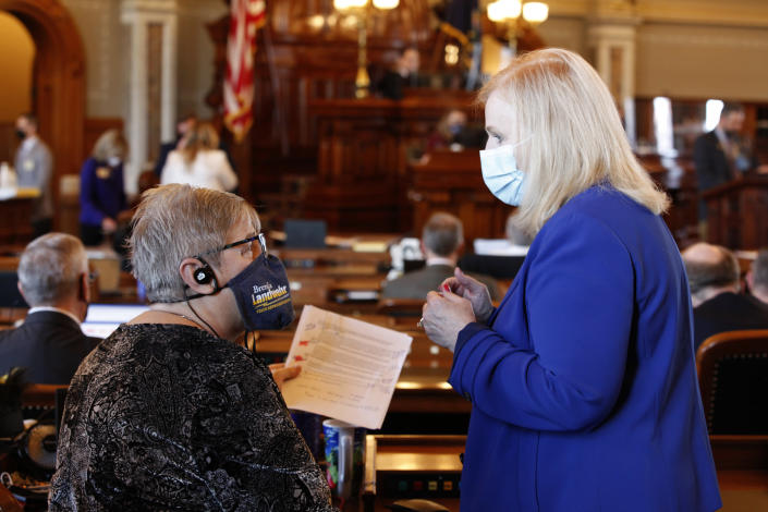 """Kansas state Reps. Brenda Landwehr, left, R-Wichita, and Susan Concannon, R-Beloit, confer during a House debate on a proposed anti-abortion amendment to the Kansas Constitution, Friday, Jan. 22, 2021, at the Statehouse in Topeka, Kan. Both supported the measure, which would overturn a Kansas Supreme Court decision in 2019 that declared access to abortion a """"fundamental"""" right under the state constitution. (AP Photo/John Hanna, Pool)"""