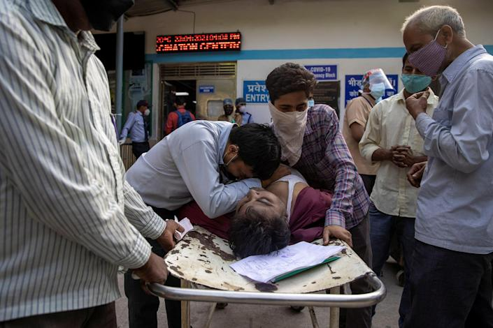"Family members mourn after Shayam Narayan, a 45-year-old COVID-19 patient and father of five, is declared dead outside the COVID-19 casualty ward at Guru Teg Bahadur Hospital in Delhi on April 23.<span class=""copyright"">Danish Siddiqui—Reuters</span>"