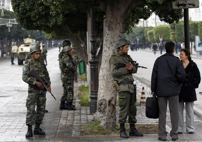 FILE - In this Tuesday Jan. 18. 2011 file photo, local residents speak with soldiers as they guard the center of Tunis. Tunisia's president on Thursday March 6, 2014, lifted the state of emergency that has been in place since the outbreak of a popular revolution three years ago, and a top military chief said soldiers stationed in some of the country's most sensitive areas will return to their barracks. (AP Photo/Christophe Ena, File)