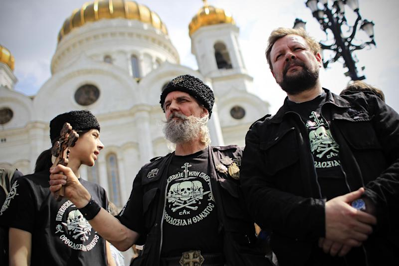 """Members of an Orthodox militant group stand in line in front of the Moscow's Christ the Savior Cathedral to prevent access of opposition activists to the Cathedral in Moscow, Sunday, April 29, 2012. Opposition activists planned to pray to Holy Mother to deliver Russia from Vladimir Putin. They planned to repeat the """"punk prayer"""" by five members of the feminist band Pussy Riot briefly who seized the pulpit of Moscow's Christ the Savior Cathedral in February and chanted """"Mother Mary, drive Putin away."""" Three band members have been arrested and now face up to seven years in jail on charges of hooliganism. (AP Photo/Sergey Ponomarev)"""