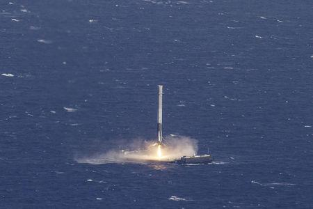 Handout photo of the reusable main-stage booster from the SpaceX Falcon 9 makes a successful landing on a platform in the Atlantic Ocean about 185 Nautical miles off the coast of Florida