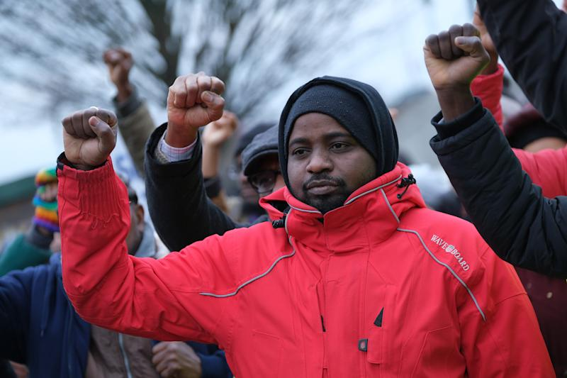 DESSAU, GERMANY - JANUARY 07: African participants sing a song while holding up their fists prior to a march to commemorate the 14th anniversary of the death of immigrant Oury Jalloh on January 7, 2019 in Dessau, Germany. Jalloh, an asylum seeker from Sierra Leone, died in a fire in a prison cell in Dessau while he was strapped to a bed in 2005. Police claim he started the fire himself, though the precise circumstances remain unclear. Two police officers went on trial but were eventually acquitted for lack of evidence. (Photo by Sean Gallup/Getty Images)