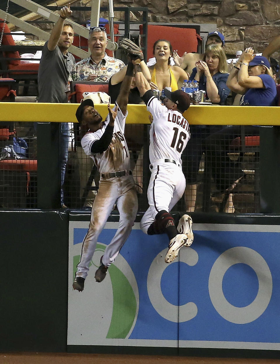 Arizona Diamondbacks center fielder Jarrod Dyson, left, makes a catch taking a home run away from Los Angeles Dodgers' Joc Pederson as Dyson collides with Diamondbacks right fielder Tim Locastro (16) during the seventh inning of a baseball game Wednesday, June 26, 2019, in Phoenix. (AP Photo/Ross D. Franklin)