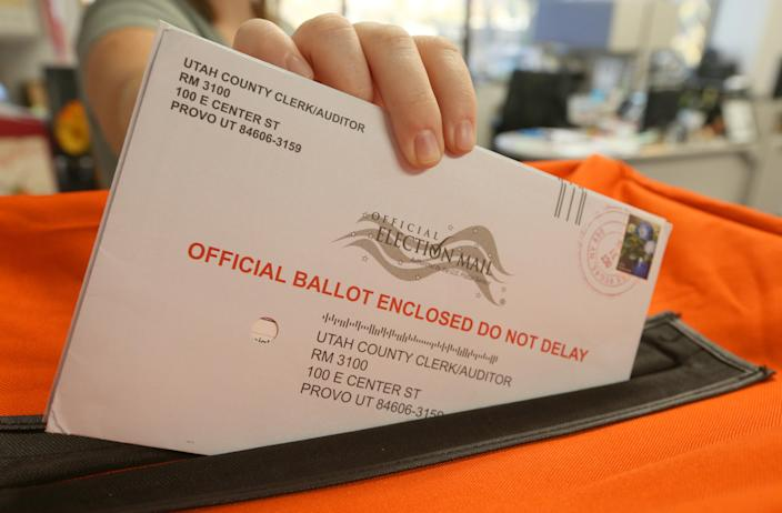 A employee at the Utah County Election office puts mail in ballots into a container to register the vote. (Photo by George Frey/Getty Images)