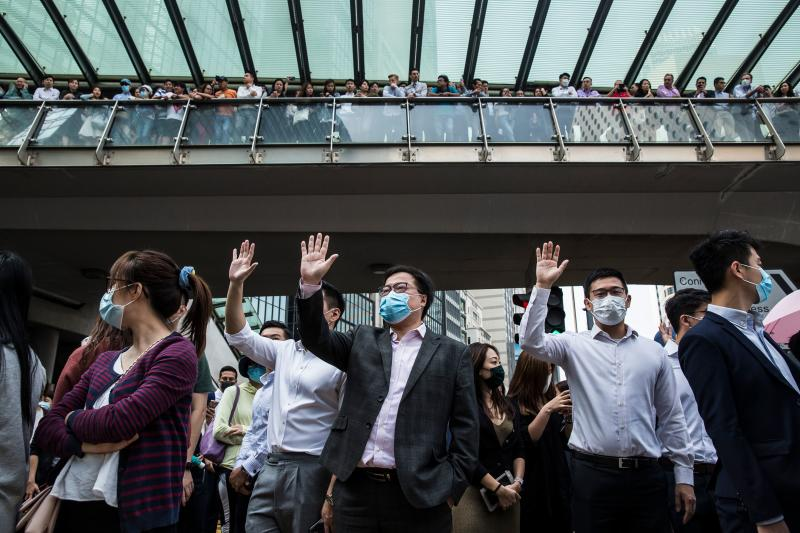 Office workers and protesters gather during a demonstration in Central in Hong Kong on November 14, 2019. - Pro-democracy protesters challenging China's rule of Hong Kong on November 14 choked the city for a fourth straight working day, firing arrows at police, barricading roads and disrupting transport links, as schools and businesses closed. (Photo by ISAAC LAWRENCE / AFP) (Photo by ISAAC LAWRENCE/AFP via Getty Images)