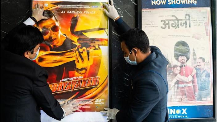Workers put up movie posters in a theatre ahead of the scheduled reopening of cinema theatres on October 15