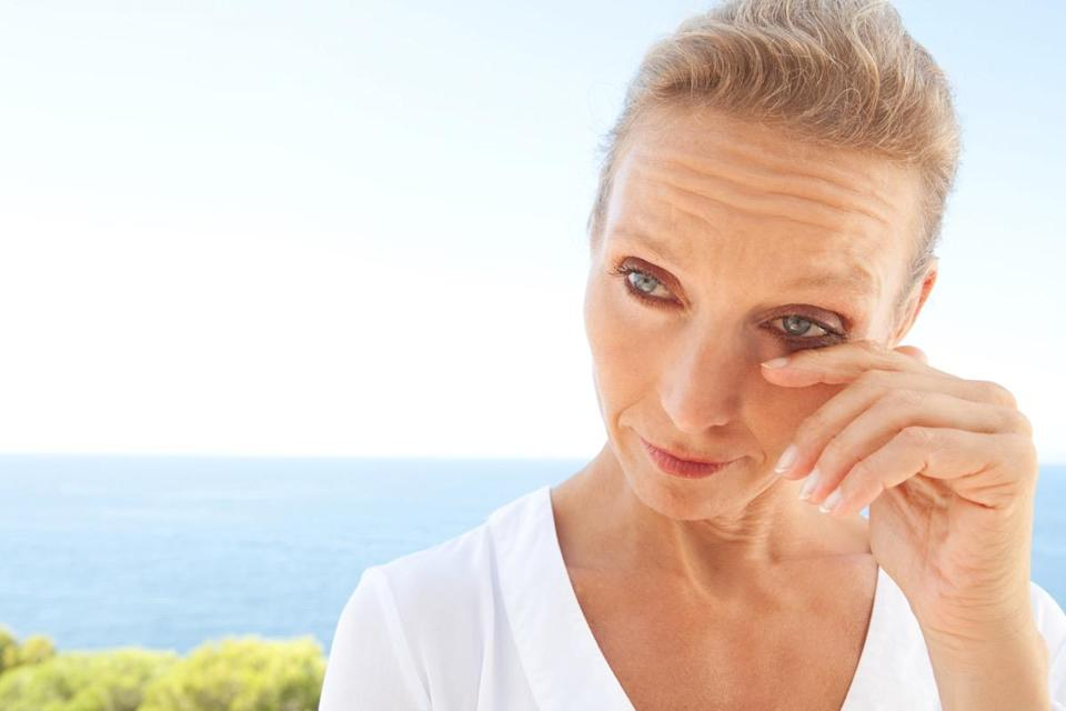 mature healthy woman with blue eyes and flawless skin crying and drying up her tears, worried and emotional. Mature and aging face with a sad expression, outdoors