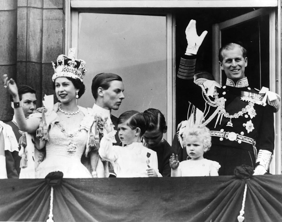 Queen Elizabeth II, Prince Philip, Prince Charles and Princess Anne wave from the balcony at Buckingham Palace after Elizabeth's coronation ceremony in London on June 2, 1953.