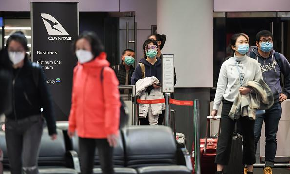 Passengers wearing face masks wait to be interviewed and temperature checked by New South Wales health officials after they arrive from a Qantas flight that flew from Melbourne at Sydney Airport in Sydney, Australia.